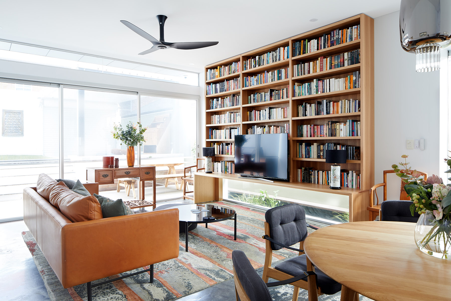 Living room with a unique bookcase over a window.