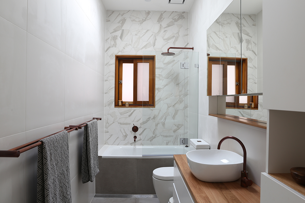Bathroom with porcelain marble tiles and copper and timber